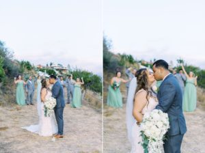 bride and groom kissing while their bridal party is in the back cheering them on